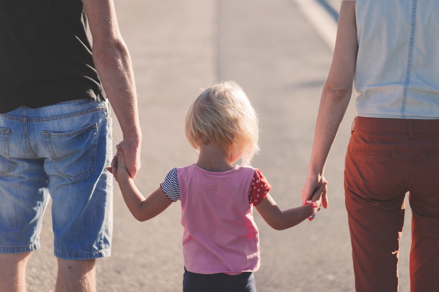 Parents walk down road with toddler daughter